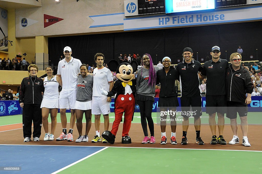 Tennis legend Billie Jean King, Marion Bartoli, John Isner, Taylor Townsend, Jean Julien Roger, Venus Williams, Vicky Duval, Robert Kendrick, Andy Roddick and singer Sir Elton John pose with Disney character Mickey Mouse during the Mylan World TeamTennis Matches at ESPN Wide World of Sports Complex on November 17, 2013 in Lake Buena Vista, Florida.