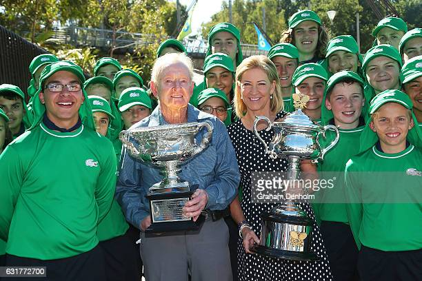Tennis legends Chris Evert and Rod Laver hold the Daphne Akhurst Memorial Cup and Norman Brookes Challenge Cup as they pose with representatives of...