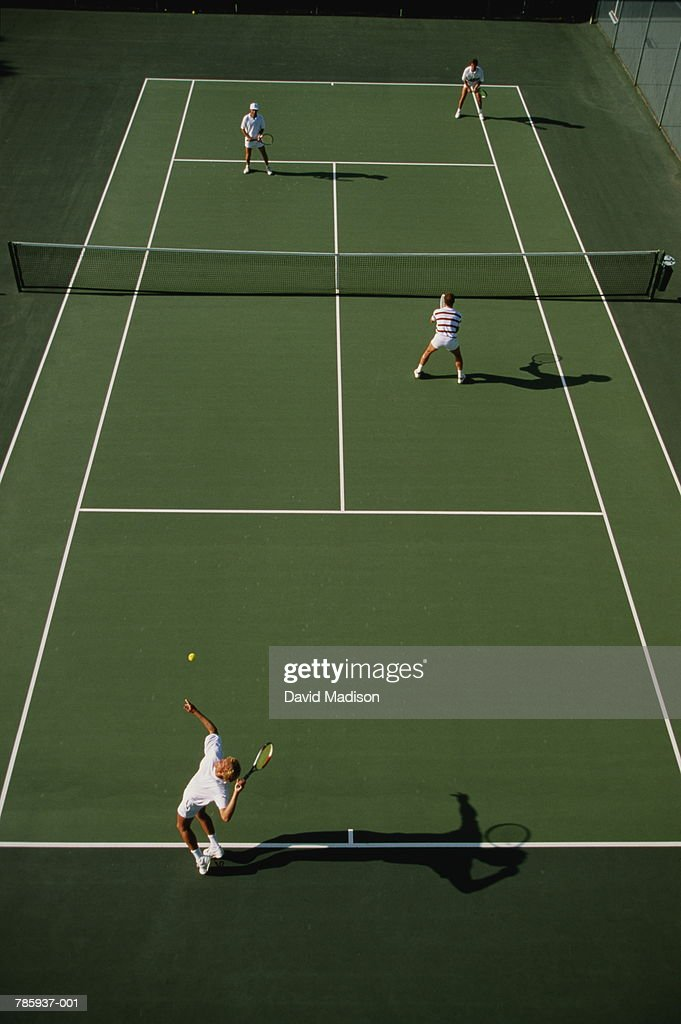 Tennis, men playing doubles on green court, elevated view : Stock Photo