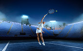 Tennis girl on a professional tennis court in night.