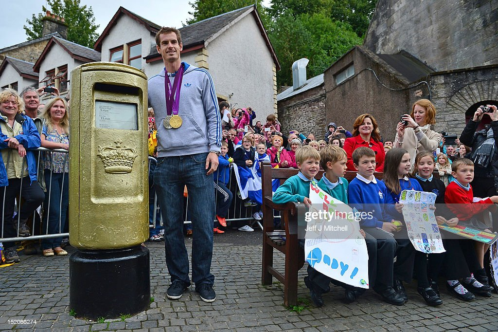 Tennis player <a gi-track='captionPersonalityLinkClicked' href=/galleries/search?phrase=Andy+Murray+-+Tennisser&family=editorial&specificpeople=200668 ng-click='$event.stopPropagation()'>Andy Murray</a> poses next to a post box which was painted gold by the Royal Mail in recognition of his gold medal, after he returned to Dunblane following his win in the US Open and his gold medal in the 2012 Olympic games in London, on September 16, 2012 in Dunblane,Scotland. Thousands lined the streets of his hometown as the 25 year old returned to meet with family and friends following his summer triumphs.