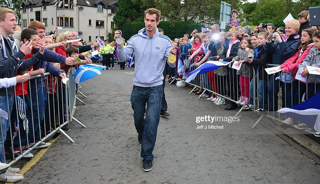 Tennis player <a gi-track='captionPersonalityLinkClicked' href=/galleries/search?phrase=Andy+Murray+-+Tennis+Player&family=editorial&specificpeople=200668 ng-click='$event.stopPropagation()'>Andy Murray</a> returns to Dunblane following his win in the US Open and his gold medal in the 2012 Olympic games in London, on September 16, 2012 in Dunblane,Scotland. Thousands lined the streets of his hometown as the 25 year old returned to meet with family and friends following his summer triumphs.