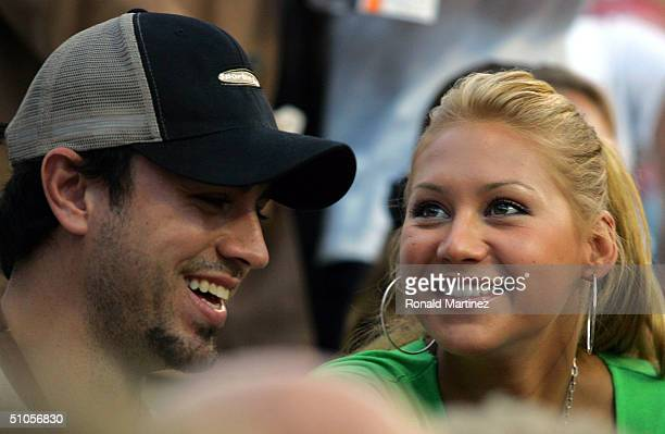 Tennis player Anna Kournikova and singer Enrique Iglesias watch Andre Agassi play against Alex Bogomolov Jr during day 2 of the MercedesBenz Cup on...