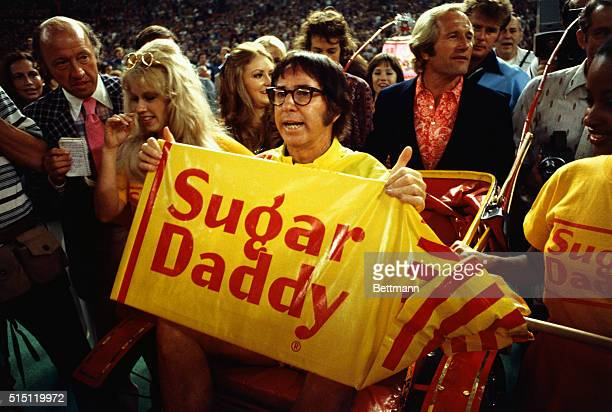 Tennis player Bobby Riggs holding a 'Sugar Daddy' sign while being carried to the court by young women He is about to play a tennis match against...