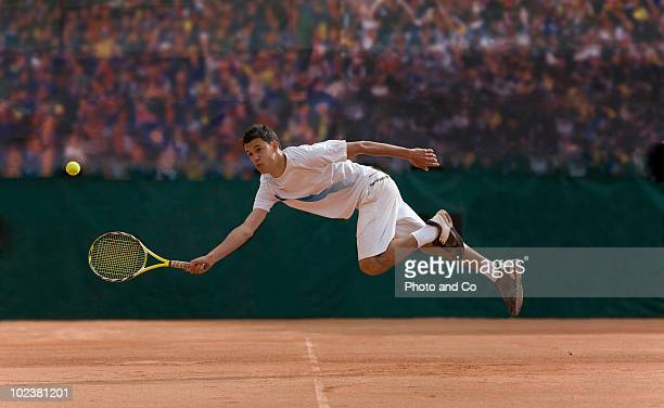 Tennis player diving to hit ball on clay court