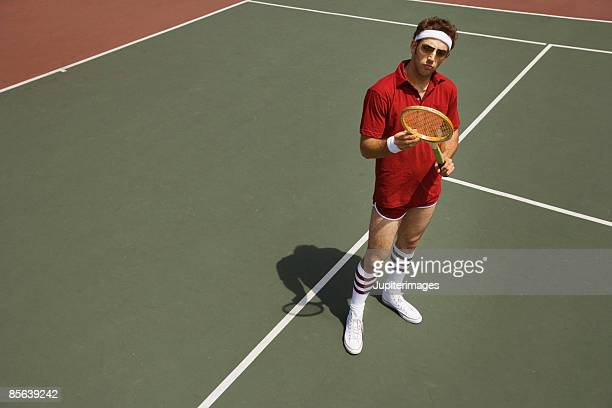 Tennis player examining tennis racquet