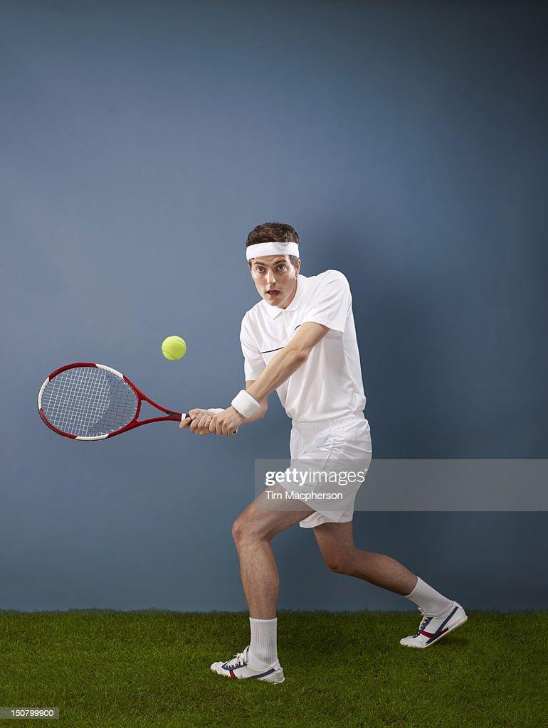 A tennis player hitting a ball : Stock Photo