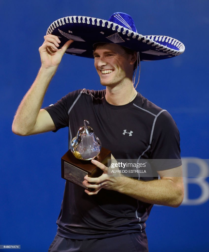 UK tennis player Jamie Murray poses with the trophy after winning with Brazilian tennis player Bruno Soares the Mexican Tennis Open doubles final match against US tennis player Feliciano Lopez and Spanish tennis player John Isner in Acapulco, Guerrero State, Mexico, on March 4, 2017. /