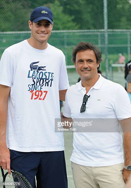 Tennis player John Isner and Lacoste President and CEO of North America Francis Pierrel attend the City Parks Foundation's tennis clinic at the...