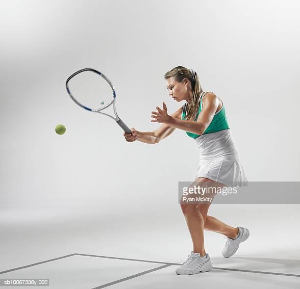 Tennis player making forehand hit (studio shot)