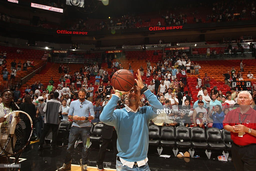 Tennis player <a gi-track='captionPersonalityLinkClicked' href=/galleries/search?phrase=Novak+Djokovic&family=editorial&specificpeople=588315 ng-click='$event.stopPropagation()'>Novak Djokovic</a> tries a hand with basketball during a game between the Charlotte Bobcats and the Miami Heat on March 24, 2013 at American Airlines Arena in Miami, Florida.