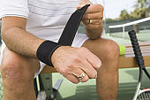 Tennis player putting on wristband