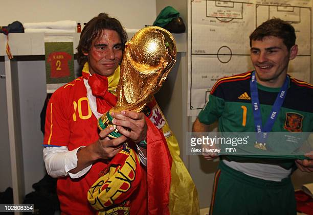 Tennis player Rafael Nadal poses with the World Cup as Iker Casillas of Spain looks on in the Spanish dressing room after they won the 2010 FIFA...