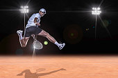 Tennis player jumping for the ball behind on clay tennis court