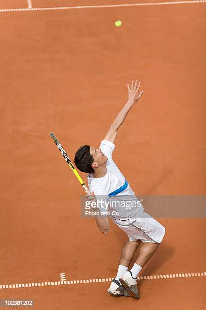 Tennis player serving on clay court