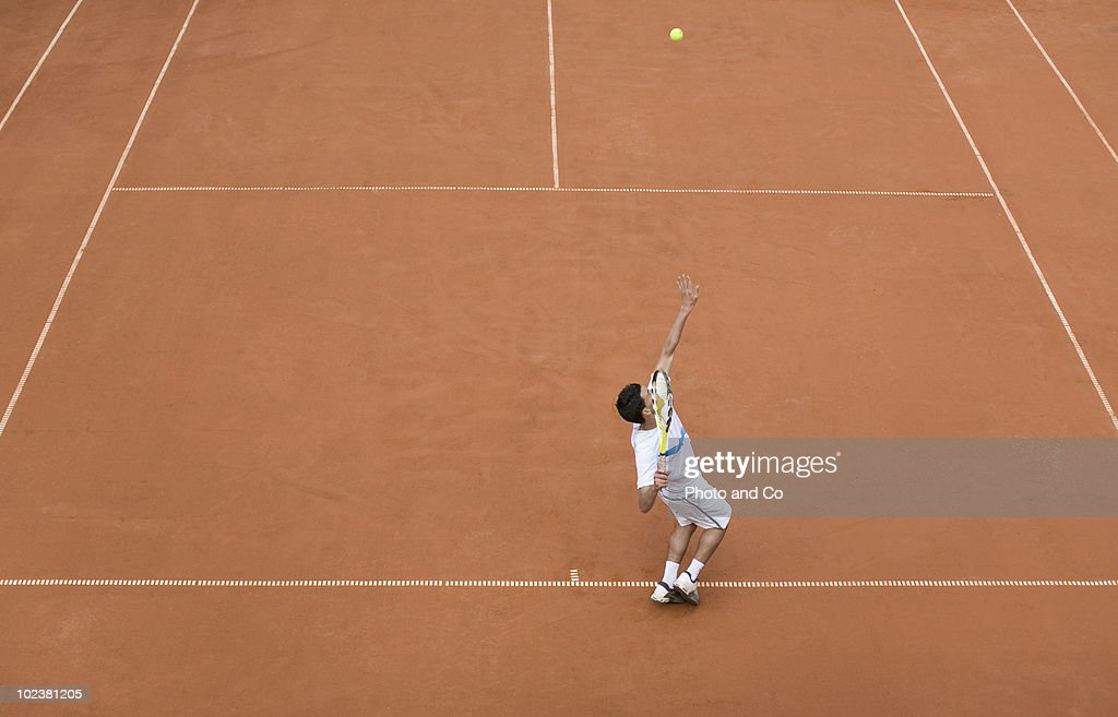 Tennis player serving on clay court : Photo