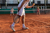 Unrecognizable tennis player serving outdoor. Tennis player with racket during a match game prepares to serve a tennis ball