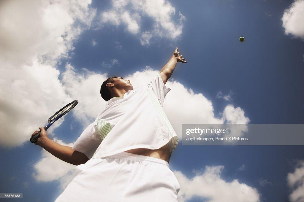 Tennis player serving tennis ball : Stock Photo