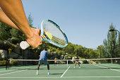 Tennis player serving tennis ball