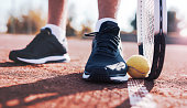 Tennis player picking ball up with racket. Sport, recreation concept