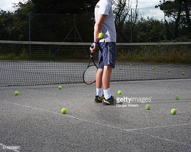 Tennis player standing on tennis court.