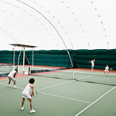Tennis players in indoor tennis court, elevated view