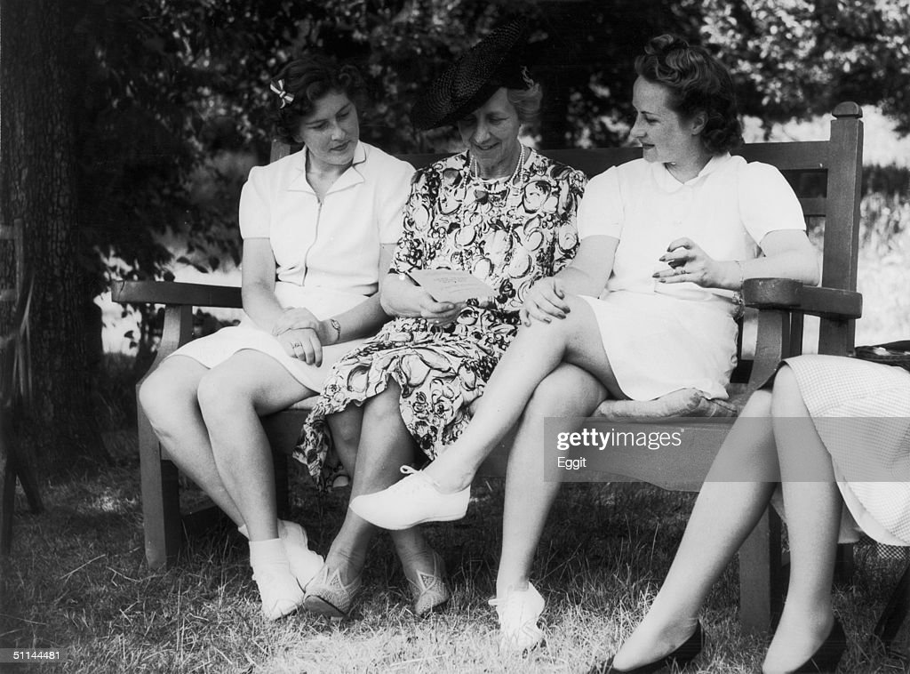 Tennis players Jean Nicoll (left) and Billie Yorke (right) share a bench with Lady Crosfield at her Highgate home, 10th July 1941. Lady Crosfield is hosting a lawn tennis tournament in aid of the Crown Princess of Greece's Comfort Fund.