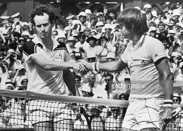 Tennis players John McEnroe and Jimmy Connors shake hands after McEnroe wins the men's singles finals at the 1984 Wimbledon in sweltering heat