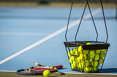 tennis balls in a basket with a racket.