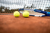 Tennis racket and balls lying at the court next to the net - outdoors sports concepts
