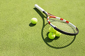 Tennis racket and four balls on the court grass