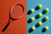 Top view shot of and tennis racket and balls placed on two toned surface