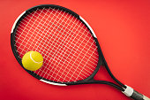 Tennis racket and tennis ball on the red clay court