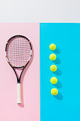 top view of tennis racket on pink and yellow balls in row on blue