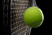 A tennis racket with tennis ball on a black background