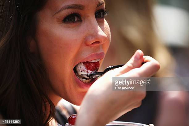 A tennis spectator eats Strawberries and cream on day two of the Wimbledon Lawn Tennis Championships at the All England Lawn Tennis and Croquet Club...