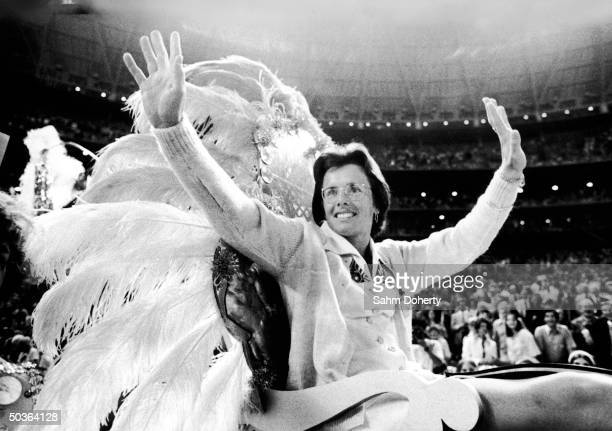 Tennis star Billie Jean King waving to fans from float as she is carried into stadium prior to her tennis match with Bobby Riggs