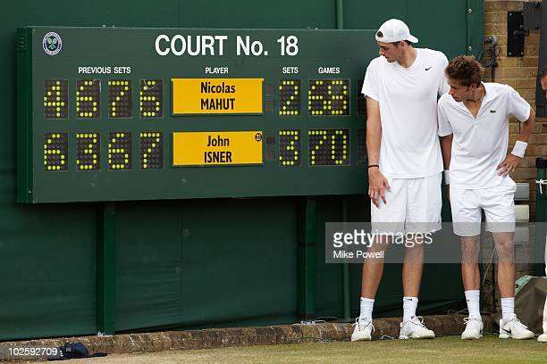 Wimbledon USA John Isner victorious near scoreboard with France Nicolas Mahut after winning Men's 1st Round at All England Club Day 3 of match Isner...