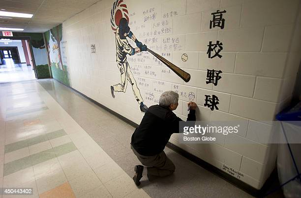 Tennoji Manager Hideshi Masa signs the mural painted by HHS students Ali Weaver and Emma McKeonWhite Members of the Tennoji High School baseball team...