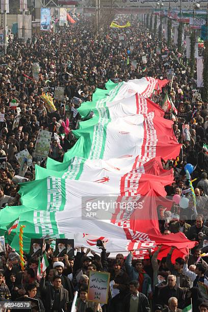 Tens of thousands of Iranians hold up a huge Iranian flag as they march in Azadi Square in southwestern Tehran to mark the 31st anniversary of the...