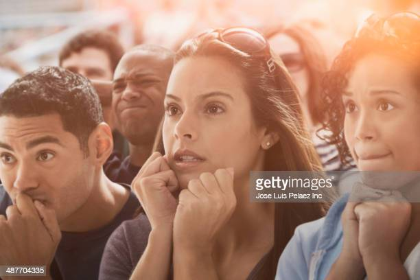 Tense spectators watching sporting event