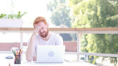 Tense, Stressed, Frustrated Man Sitting in Outdoor Office, Red Hairs