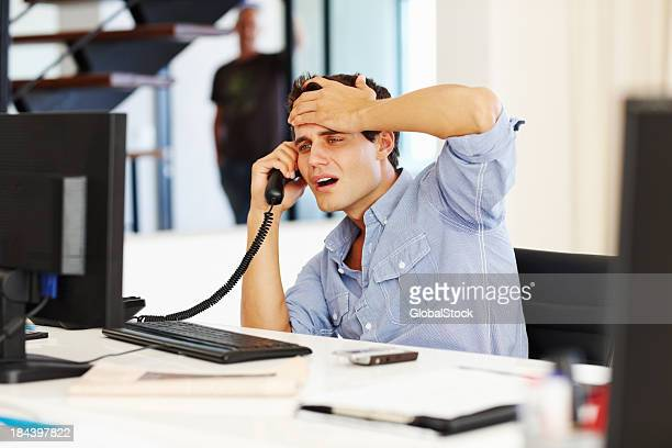 Tensed business man on call while looking at computer