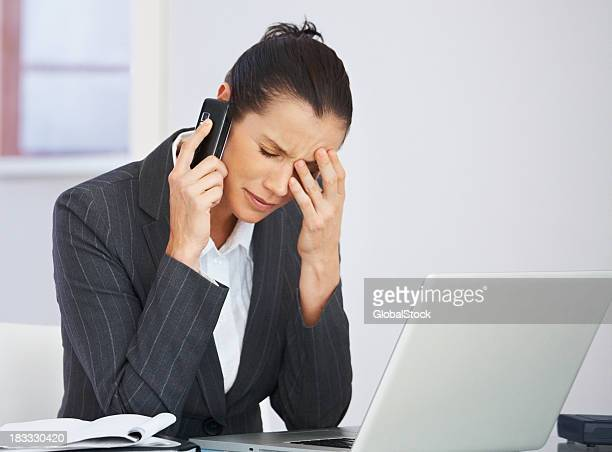 Tensed middle aged business woman using a cellphone at work