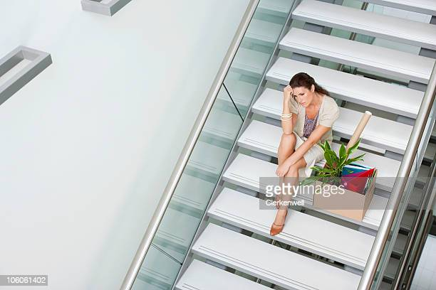 Tensed woman sitting on staircase with cardboard box
