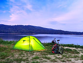 tent and bike on the lake after sunset