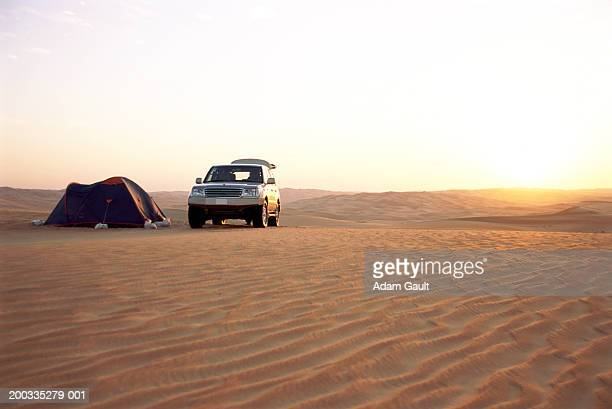 Tent by 4x4 vehicle in desert landscape