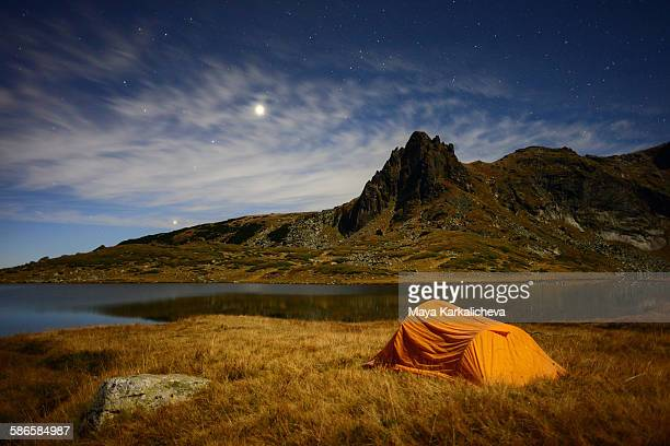 Tent by a lake in a mountain at full moon light