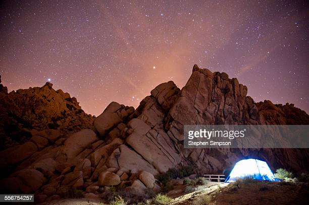 tent glowing under starry sky in the desert
