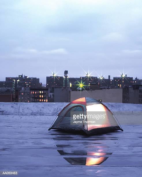 Tent illuminated on urban rooftop, twilight